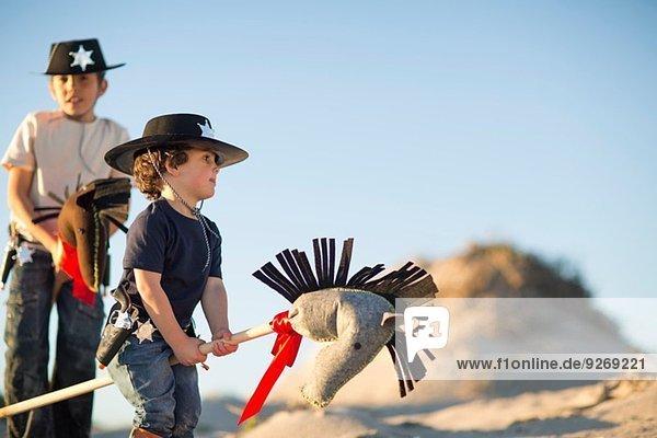 Zwei Brüder verkleidet als Cowboys mit Hobbypferden in Sanddünen