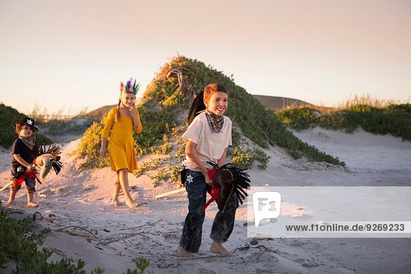 Three children dressed as native american and cowboys running in sand dunes