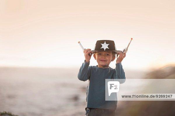 Junge als Cowboy-Sheriff verkleidet  hält sich an Hut und Spielzeugpistolen in Sanddünen fest.