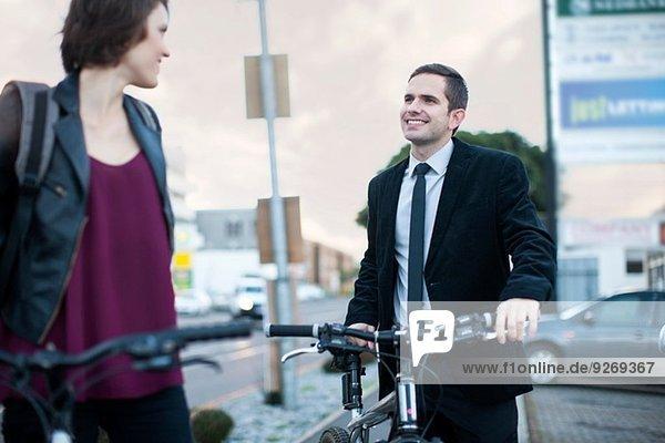 Junge Frau im Gespräch mit Geschäftsmann beim Radfahren zur Arbeit