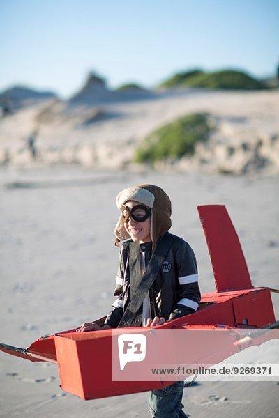 Junge läuft mit Spielzeugflugzeug in Sanddünen