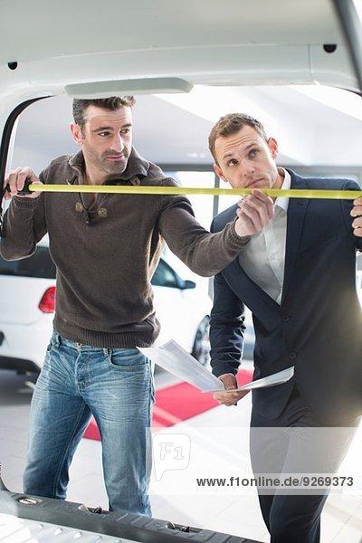 Kunde und Verkäufer bei der Vermessung von Fahrzeuginnenräumen im Autohaus