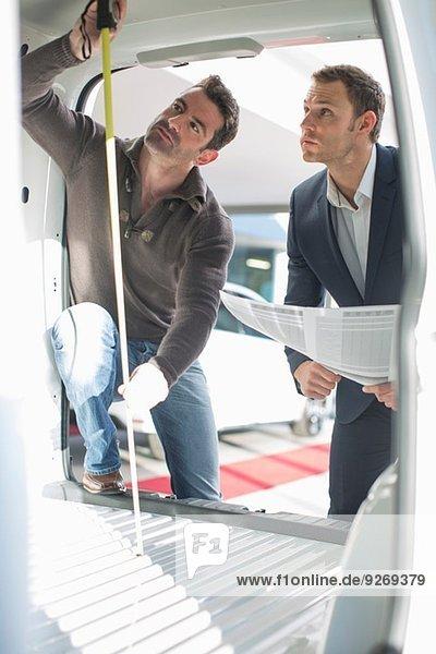 Kunde und Verkäufer prüfen Fahrzeuginnenhöhe im Autohaus