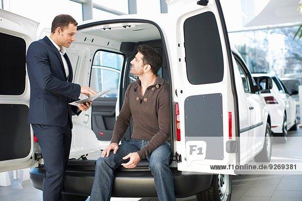 Unentschlossener Kunde und Verkäufer im Autohaus