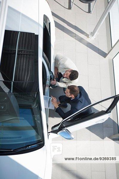 Overhead-Ansicht des Verkäufers und Kunden bei der Neuwageninspektion im Autohaus