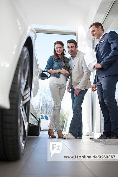 Mittleres erwachsenes Paar und Verkäufer  der sich das Auto im Autohaus ansieht.
