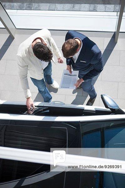 Overhead-Ansicht des Verkäufers und Kunden bei der Suche nach Neuwagen im Autohaus