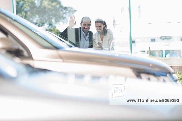 Mittleres erwachsenes Paar  das durch das Autohausfenster schaut