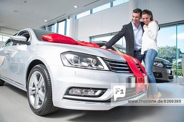 Mann sucht neues Auto mit roter Schleife mit Freundin im Autohaus