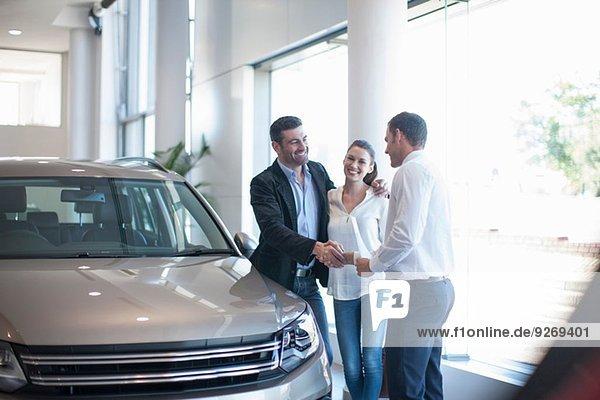 Verkäufer beim Händeschütteln mit erwachsenem Paar im Autohaus