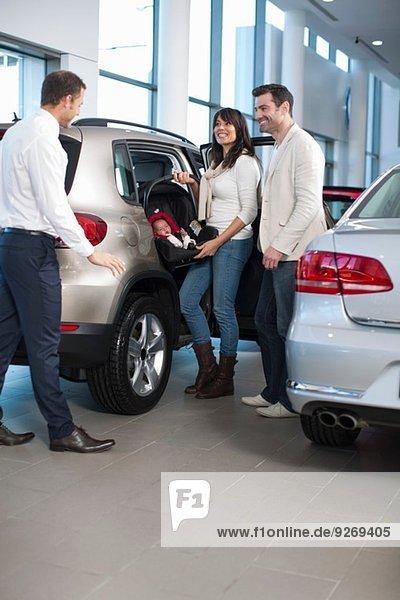 Verkäufer im Gespräch mit der Familie mit dem kleinen Mädchen im Autohaus