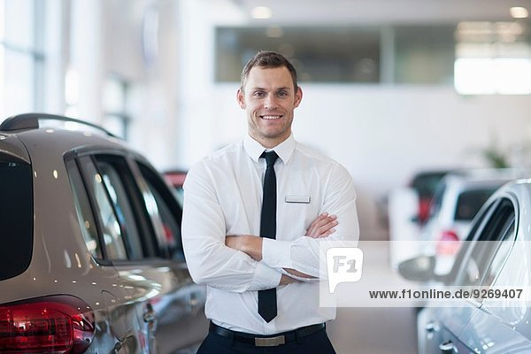 Porträt eines lächelnden Verkäufers im Autohaus