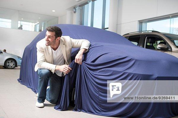 Mittlerer Erwachsener Mann  der das neue Auto im Autohaus aufdeckt und anschaut.