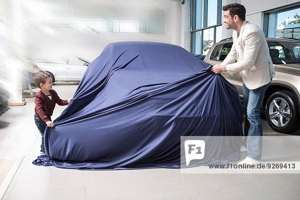 Mittlerer Erwachsener Mann entdeckt neues Auto mit Sohn im Autohaus
