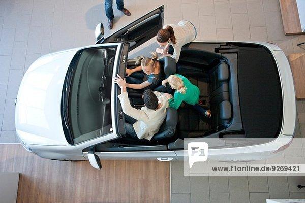 Overhead-Ansicht der Familie beim Ausprobieren des Cabrios im Autohaus