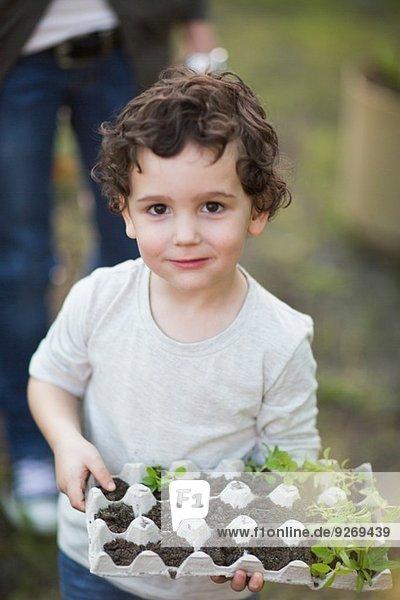 Portrait des Jungen mit Eierkarton und Pflanzen im Garten
