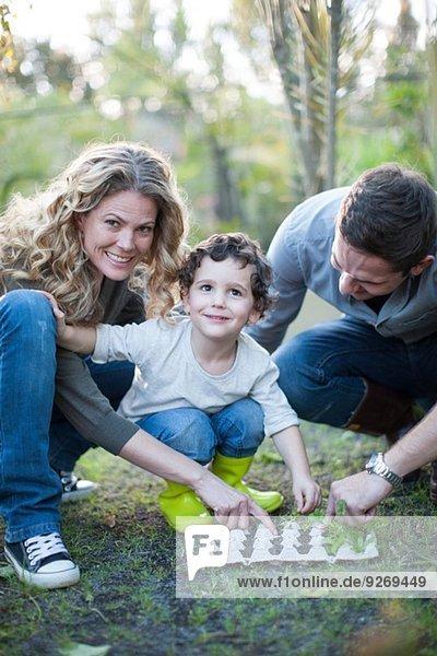 Mittleres Paar und Sohn pflanzen in Eierkartons auf Zuteilung