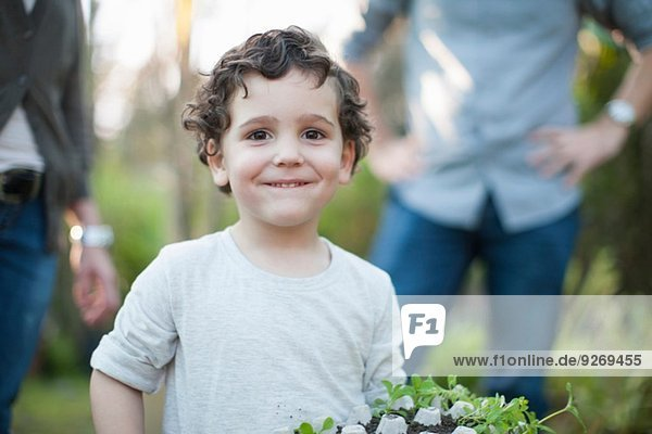 Portrait des Jungen mit Pflanzen im Eierkarton im Kleingarten