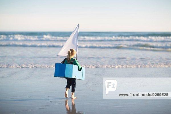 Mädchen rennt mit Spielzeugboot ins Meer Mädchen rennt mit Spielzeugboot ins Meer
