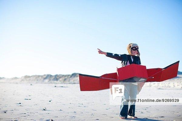 Junge steht mit einem Spielzeugflugzeug und zeigt auf den Strand.