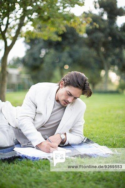 Geschäftsmann auf Picknickdecke liegend  Notizen im Park schreibend