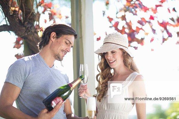 Paare trinken Champagner in der Gartenweinbar