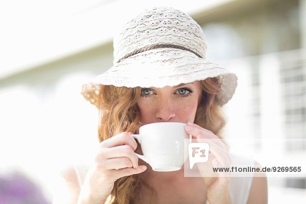 Porträt einer jungen Frau  die aus einer Kaffeetasse im Straßencafé trinkt.