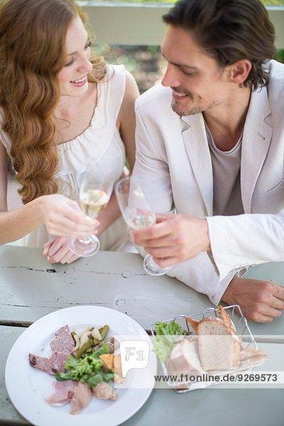 Pärchentoast mit Champagner bei Tisch im Gartenrestaurant
