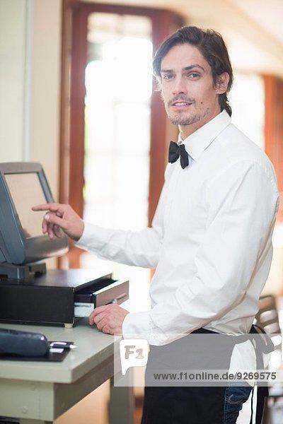 Portrait of waiter using touch screen on cash register in restaurant