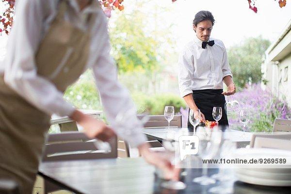 Kellnerin bei der Zubereitung von Weingläsern auf dem Tisch im Terrassenrestaurant