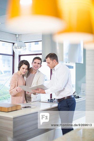 Mittleres erwachsenes Ehepaar und Verkäufer beim Betrachten der Broschüre im Küchen-Showroom