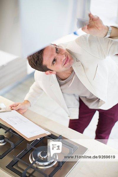 Mittelgroßer Mann mit Blick auf Dunstabzugshaube im Küchenstudio
