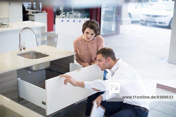 Kundin und Verkäuferin mit Blick auf die Schublade im Küchen-Showroom