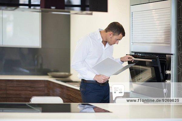 Mittlerer Erwachsener Mann  der den Ofen in der Küche inspiziert.