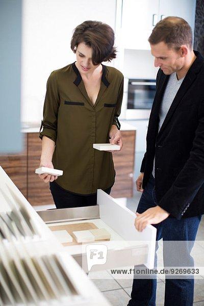 Mittleres erwachsenes Paar beim Betrachten von Keramikfliesen im Küchen-Showroom