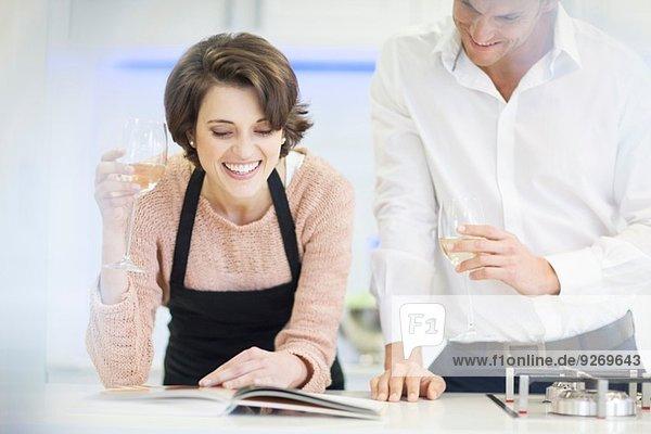 Paar Trinkglas Weißwein beim Lesen des Rezeptbuches in der Küche