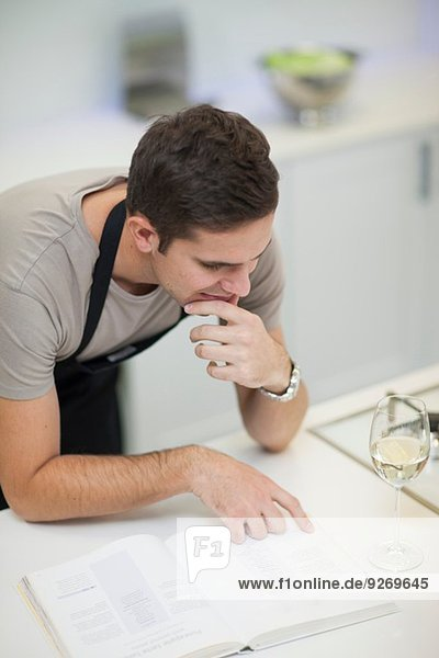 Mann liest Rezept im Kochbuch