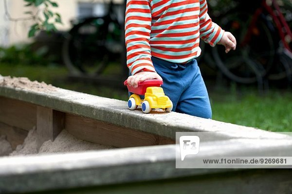 Ausschnitt eines männlichen Kleinkindes  das ein Spielzeugauto um eine Sandgrube im Garten schiebt.