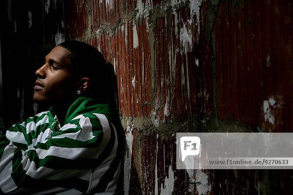 sitzend Mann Wand Ziegelstein jung