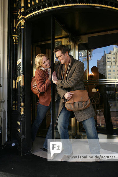 Mature couple playing with revolving doors
