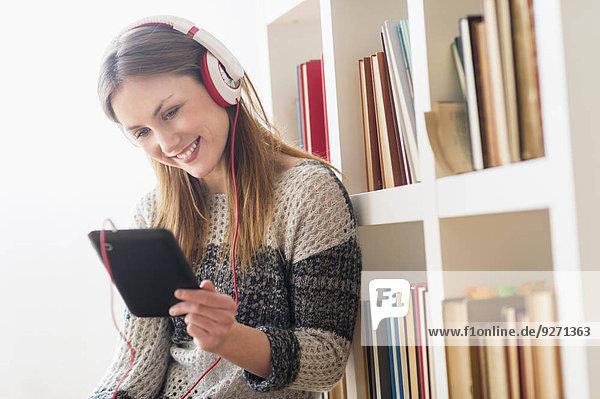 sitzend junge Frau junge Frauen zuhören Boden Fußboden Fußböden Musik Tablet PC Klassisches Konzert Klassik