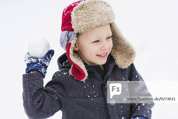 Boy (6-7) playing with snowball