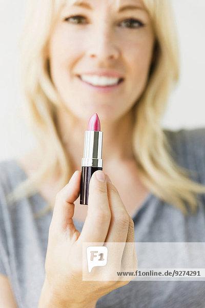 Portrait Frau Lippenstift halten pink Studioaufnahme blond