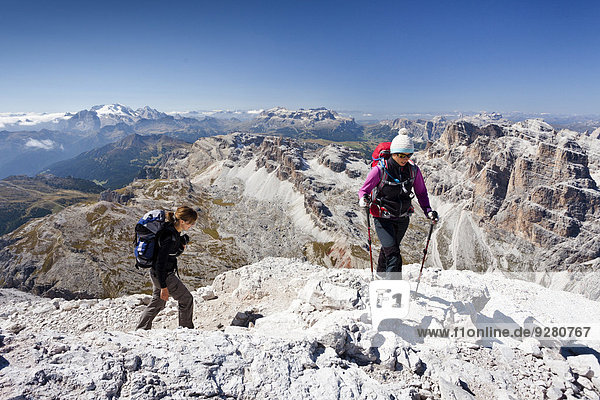 Bergsteiger beim Aufstieg auf die Tofana di Rozes über die Via ferrata Giovanni Lipella  hinten der Sellastock und das Grödnerjoch  links die Marmolata  Dolomiten  Cortina d'Ampezzo  Belluno  Venetien  Italien