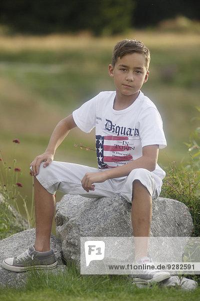 Boy  9 years old  sitting on rock