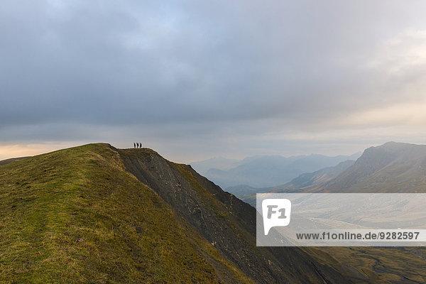 Drei Wanderer auf dem Grat eines Berges in den Pelvoux in der Dämmerung  Dauphiné-Alpen  Département Savoie  Frankreich