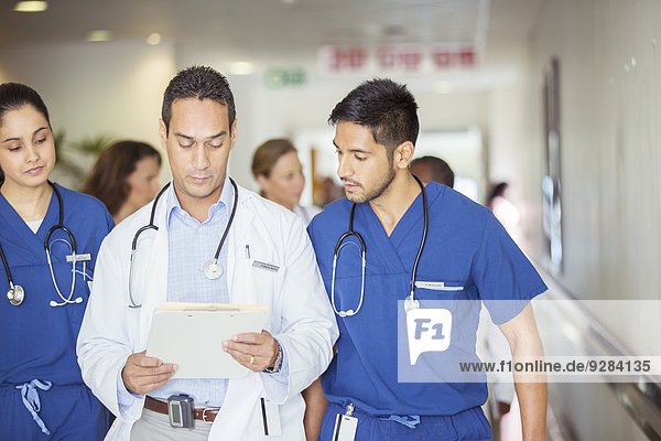 Doctor and nurses reading medical chart in hospital hallway