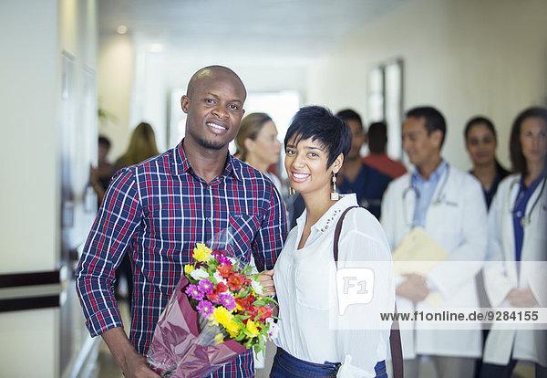 Paar mit Blumenstrauß im Krankenhaus