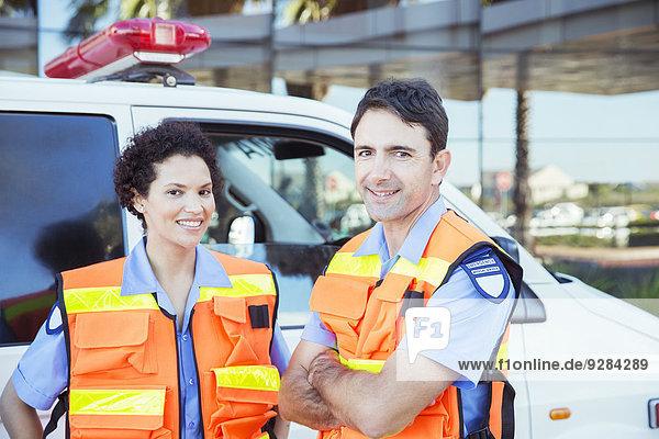 Sanitäter lächeln vor dem Krankenwagen