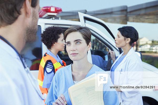 Arzt und Krankenschwester im Gespräch außerhalb des Krankenhauses